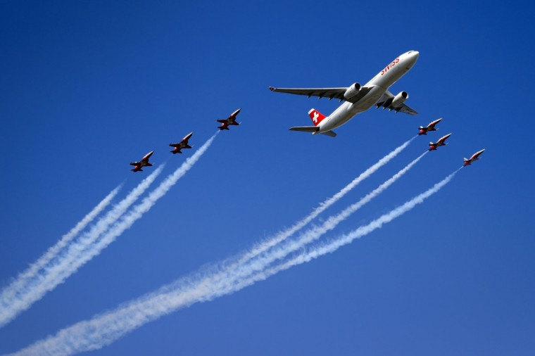 "An Airbus A330 commercial plane of Swiss International Air Lines flies with fighter jets of the ""Patrouille Suisse"" (Swiss patrol) during the second weekend of the AIR14 air show on September 6, 2014 in Payerne, western Switzerland. (FABRICE COFFRINI/AFP/Getty Images)"