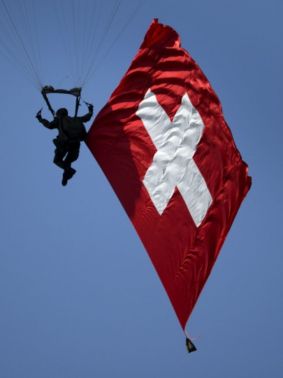 A Swiss Army Parachutist performs with a giant national flag during the second weekend of the AIR14 air show on September 6, 2014 in Payerne, western Switzerland. (FABRICE COFFRINI/AFP/Getty Images)