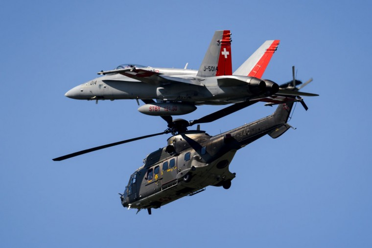 An F/A-18 Hornet fighter jet flies with a Super Puma Helicopter, both from the Swiss Air Force, during the second weekend of the AIR14 air show on September 6, 2014 in Payerne, western Switzerland. (FABRICE COFFRINI/AFP/Getty Images)