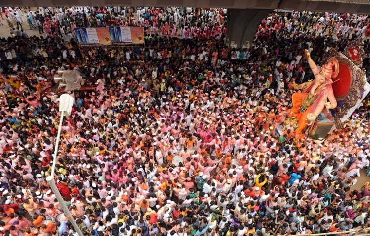 Indian devotees throng the streets as a huge idol of elephant-headed Hindu god Lord Ganesha is brought on procession for an immersion in Mumbai on September 8, 2014. Hindu devotees take idols of the Lord Ganesha - believed to be the harbinger of good health, prosperity and wisdom, at the end of the ten-day long Ganeshotsav festival to be immersed in water bodies. (Indranil Mukherjee/AFP/Getty Images)