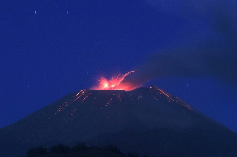 A long exposure photo shows smoke rising as lava flows from the crater of Mount Slamet volcano before dawn, as seen from Brebes town in Indonesia's Central Java province on September 12. Indonesian authorities have put the Mount Slamet volcano on the second-highest alert level after it erupted 38 times on September 11, spewing lava some 1500 metres (5,000 feet) into the air. Authorities warned residents to remain outside a four-kilometre radius of the volcano.  ||PHOTO CREDIT: AFP/Getty Images