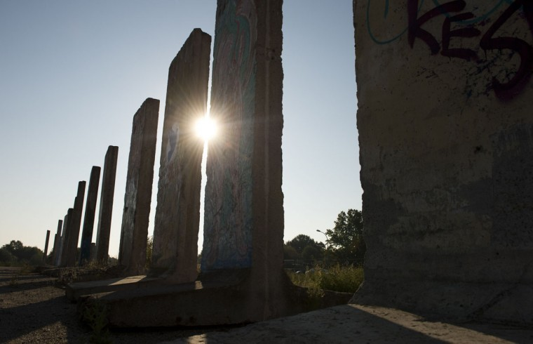 The sun shines between cement slabs that used to make up the Berlin wall stand in a vacant lot in Teltow outside of Berlin on September 18, 2014. A construction company purchased parts of the wall and offers the possibility to paint them legally after applying for it. (Photos by John MacDougall/AFP/Getty Images)