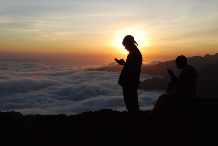 Tanzanian porters and guides stand on a rock half way up Kilimanjaro at sunset on September 21, 2014 trying to get a mobile phone signal to call their wives. Two teams are taking part in a grueling eight-day trek up the vast extinct volcano, to play a full Twenty20 game in the ice-covered crater just below its rugged peak, at 5,785 metres (19,000 feet). (Peter Martell/AFP/Getty Images )