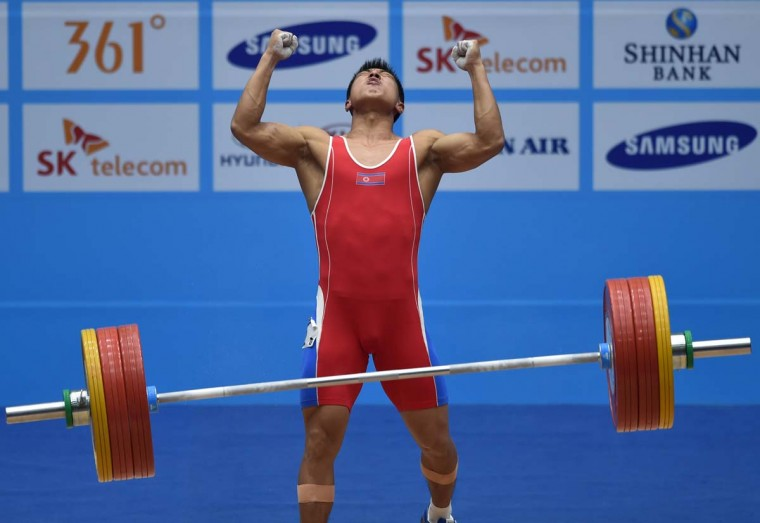 North Korean's Kim Myong-Hyok after completing a lift in the men's 69kg group A category at the Moonlight Festival Garden Weightlifting Venue during the 2014 Asian Games in Incheon on September 22, 2014. (Bay Ismoyo/AFP/Getty Images)