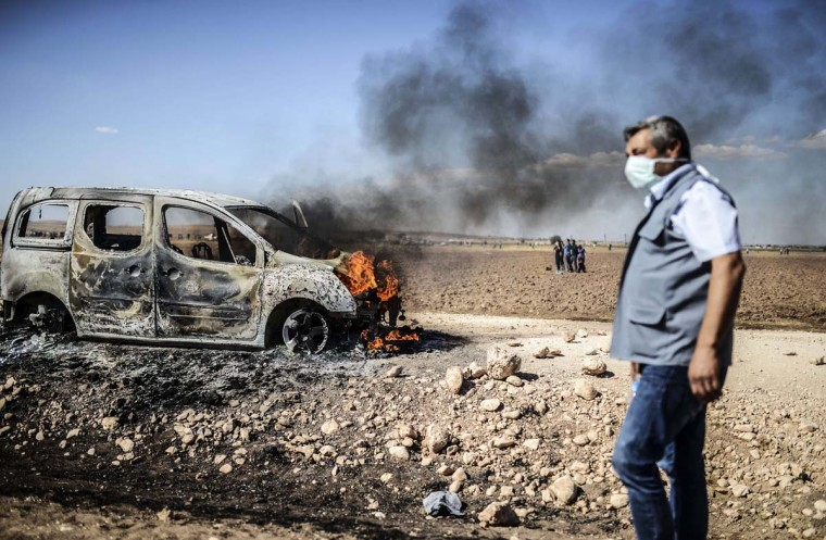 A man walks past a burning car as Kurdish protestors clashed with Turkish soldiers near the Syrian border after Turkish authorities temporarily closed the border at the southeastern town of Suruc in Sanliurfa province, on September 22, 2014. Turkey said on September 22 that some 130,000 people had flooded across its border from Syria as Kurdish fighters battled Islamic State group jihadists trying to capture a strategic town. (Bulent Kilic/AFP/Getty Images)