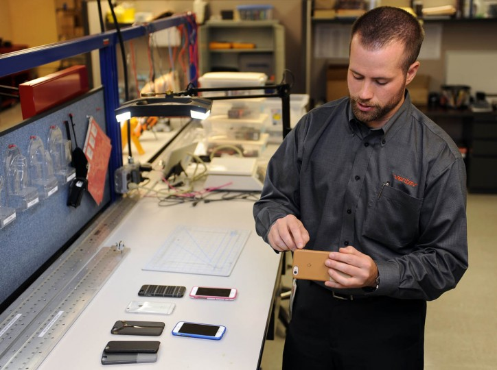 "Dave Schweitzer, quality manager for Ventev Mobile, checks the fit of a ""Penna"" leather case his company manufactured to fit the new iPhone 6, which was just released today. He and other employees at Ventev Mobile, a division of TESSCO, checked out the new iPhone for the first time today to see if it fits in the cases (and other accessories) that the company manufactures. Some of the company's other cases are on the table at left. (Barbara Haddock Taylor, Baltimore Sun)"