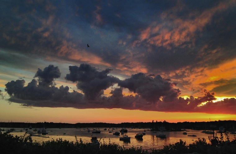A sunset filled with all hues paints the sky and water filled with boats at Boothbay Harbor. (Karl Merton Ferron/Baltimore Sun)