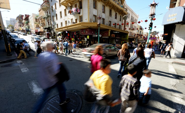 Hundreds of people walk through Chinatown in San Francisco.