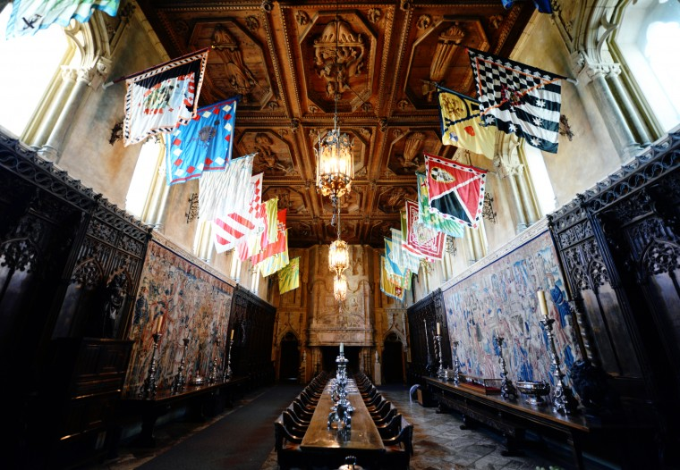 The dining room in the Hearst Castle is lined with flags and features a table dozens of feet long.