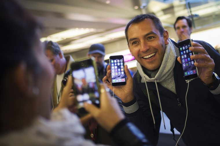 Michele Mattana of Sardinia, Italy, poses with an iPhone 6 Plus and an iPhone 6 on the first day of sales at the Fifth Avenue store in Manhattan, New York September 19, 2014. Adrees Latif/Reuters photo