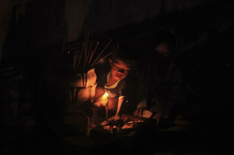 A boy makes an offering of food at a pagoda during the Pchum Ben festival in Phnom Penh September 16, 2014. Cambodians visit temples during the 15-day Pchum Ben, or Festival of the Dead, to offer prayers to loved ones who have passed away. (REUTERS/Samrang Pring)