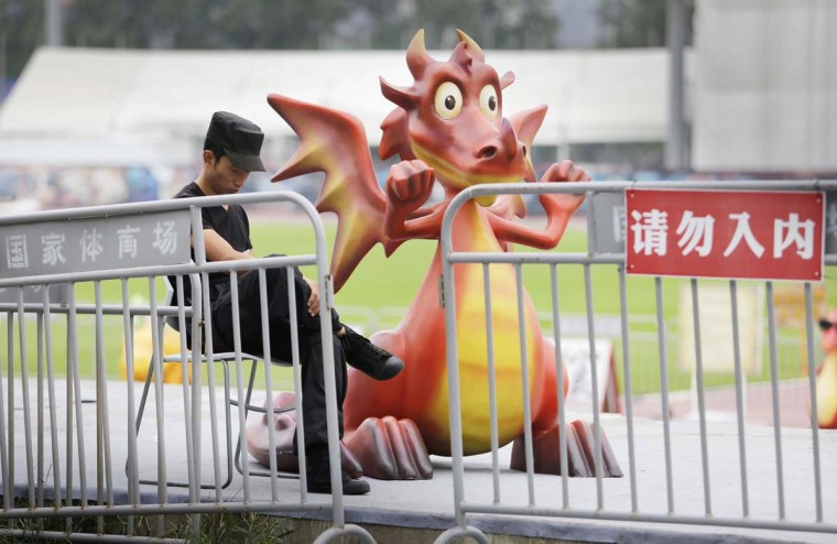 """A security guard looks at his mobile phone next to a sculpture of a dragon character from a cartoon, at an entrance of a movie theme park of """"How to Train Your Dragon"""" in Beijing, September 12. The red sign reads, """"Do not enter"""".  