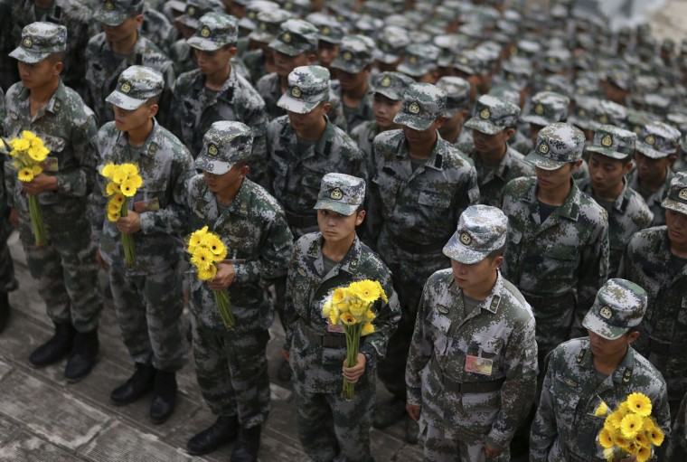 People's Liberation Army (PLA) soldiers hold flowers during a memorial ceremony ahead of China's National Day in Jinping, Yunnan province, September 30, 2014. (REUTERS/Wong Campion)