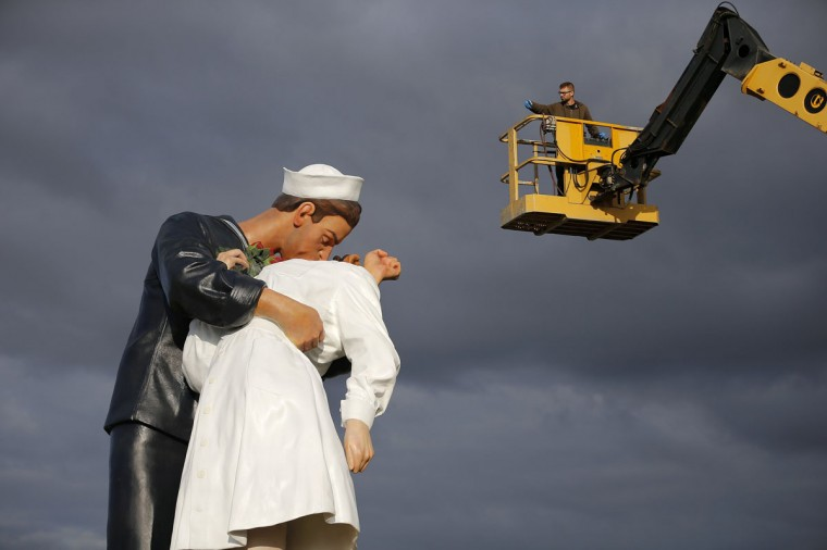 """A worker takes a picture of the """"Unconditional Surrender"""" sculpture by artist Seward Johnson of the U.S. during its installation outside the Memorial of Caen museum in Caen, September 25, 2014. The 25-foot statue of a sailor kissing a nurse is to spend a year in front of the Caen Memorial, a museum known for its extensive collection documenting the Normandy invasion in 1944 and World War II. (REUTERS/Stephane Mahe)"""