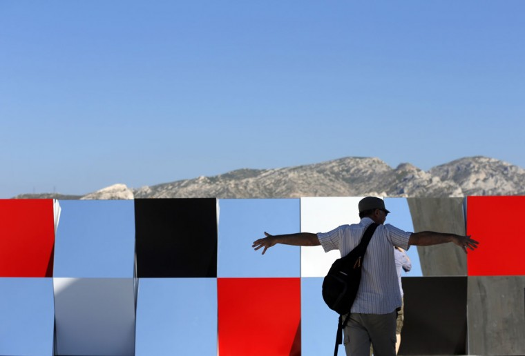 """A visitor gestures as he walks past a creation as part of the exhibition """"Defini Fini Infini, Travaux in situ"""" by French artist Daniel Buren at the MaMo art center in Marseille September 12, 2014. (Photos by Jean-Paul Pelissier/Reuters)"""