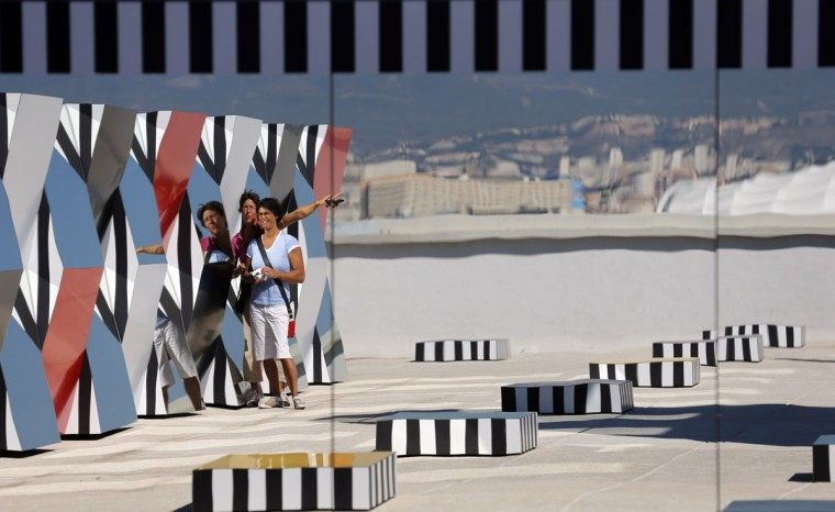 """Visitors are reflected in a creation as part of the exhibition """"Defini Fini Infini, Travaux in situ"""" by French artist Daniel Buren at the MaMo art center in Marseille September 12, 2014. (Photos by Jean-Paul Pelissier/Reuters)"""