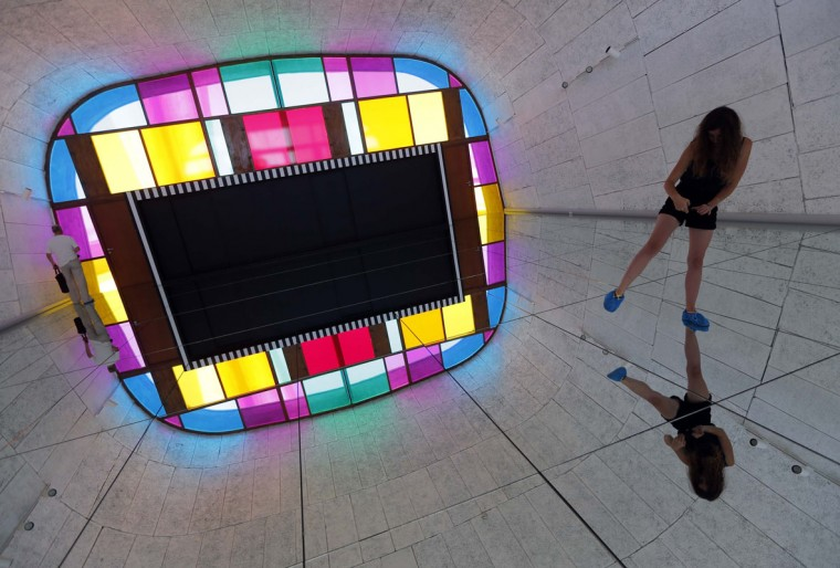 """A visitor takes a picture as she walks on a creation as part of the exhibition """"Defini Fini Infini, Travaux in situ"""" by French artist Daniel Buren at the MaMo art center in Marseille September 12, 2014. (Photos by Jean-Paul Pelissier/Reuters)"""