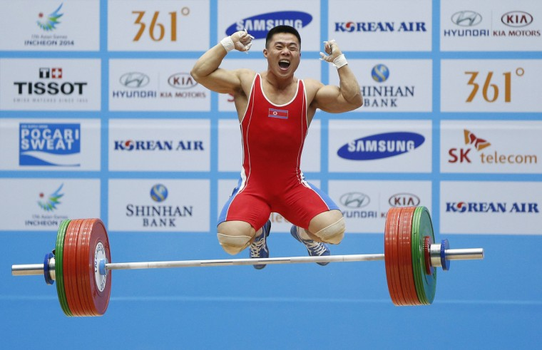 North Korea's Kim Unguk celebrates after breaking his own world record for the men's snatch 62kg weightlifting competition after lifting 154kg on his third attempt at the Moonlight Garden Venue during the 17th Asian Games in Incheon. (Olivia Harris/Reuters)