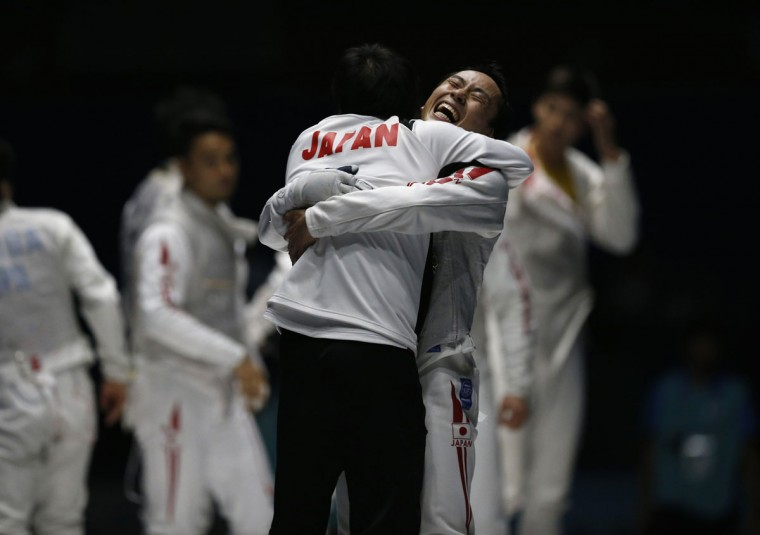 Japan's Yuki Ota (R) celebrates with a team member after winning their men's foil team fencing competition final against China at Goyang Gymnasium during the 17th Asian Games in Incheon September 25, 2014. (REUTERS/Issei Kato)