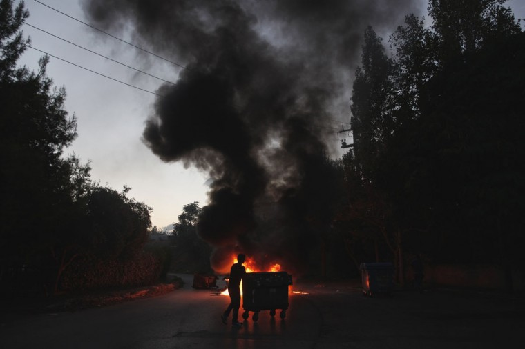 A Greek Roma is silhouetted as he pushes a garbage bin in front of burning tyres, that serve as a barricade to block bulldozers, during a protest in Athens, September 30, 2014. According to local media, a state decision to demolish and transfer a Roma camp from the northern suburb of Halandri, which it has occupied for 40 years, to Megara in West Attica caused members of the Roma community to show their dissatisfaction by torching rubber tyres and blocking traffic. (REUTERS/Alkis Konstantinidis)