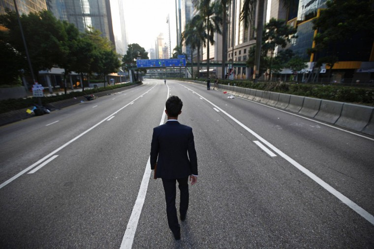 A man walks along an empty street near the central financial district in Hong Kong September 30, 2014. Tens of thousands of pro-democracy protesters extended a blockade of Hong Kong streets on Tuesday, stockpiling supplies and erecting makeshift barricades ahead of what some fear may be a push by police to clear the roads before Chinese National Day. (REUTERS/Carlos Barria)