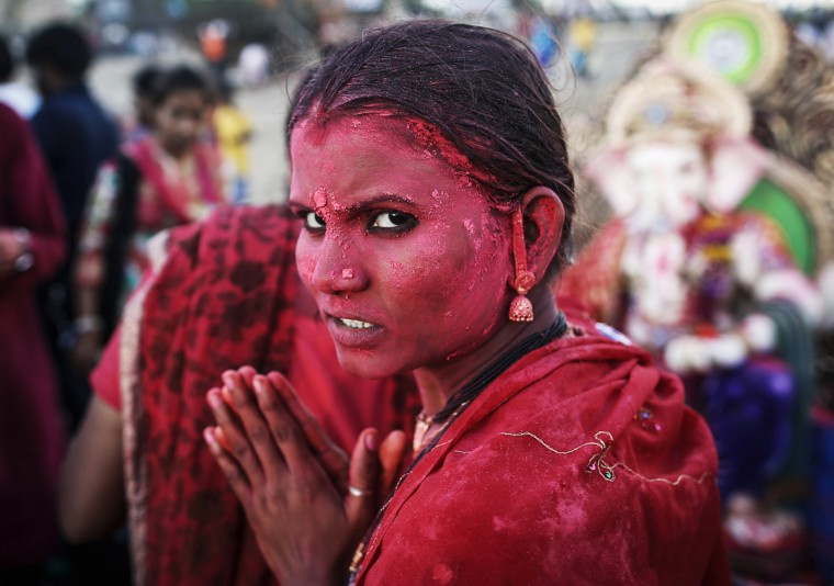 A devotee daubed in coloured powder prays as she takes part in the immersion of the idols of the Hindu god Ganesh, the deity of prosperity on the fifth day of the ten-day-long Ganesh Chaturthi festival in Mumbai September 2, 2014. Ganesh idols are taken through the streets in a procession accompanied by dancing and singing, and later immersed in a river or the sea, symbolising a ritual seeing-off of his journey towards his abode, taking away with him the misfortunes of all mankind. (REUTERS/Danish Siddiqui)