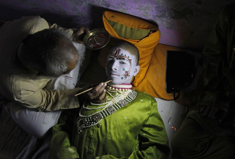 "Amit Kumar, 14, a performer, gets makeup applied before performing the role of the Hindu lord Rama in a religious play ahead of Dussehra in the northern Indian city of Allahabad September 30, 2014. Effigies of the 10-headed demon king ""Ravana"" are burnt on Dussehra, the Hindu festival that commemorates the triumph of Lord Rama over the Ravana, marking the victory of good over evil. (REUTERS/Jitendra Prakash)"