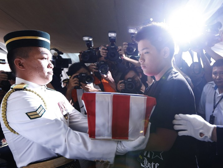 Melvic Choo, 13, takes the ashes of his father MH17 co-pilot Eugene Choo at his wake in Seremban September 2, 2014. Malaysia Airlines (MAS) Flight MH17 crashed after being shot down over war-torn Ukraine on July 17, killing all 298 people on board. (REUTERS/Olivia Harris)