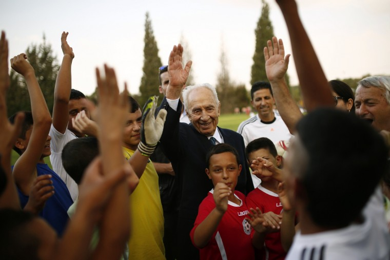 Former Israeli president Shimon Peres (C) is seen with Israeli and Palestinian children during an event opening a year of training of an Israeli-Palestinian soccer program launched by the Peres Center for Peace, in Kibbutz Dorot, outside the Gaza Strip, September 1, 2014. An open-ended ceasefire in the Gaza war has held since August 27. Some 80 children from communities near the Gaza border and from the West Bank Palestinian village of Yatta took part in the training session, the first since the ceasefire started. (REUTERS/Amir Cohen)