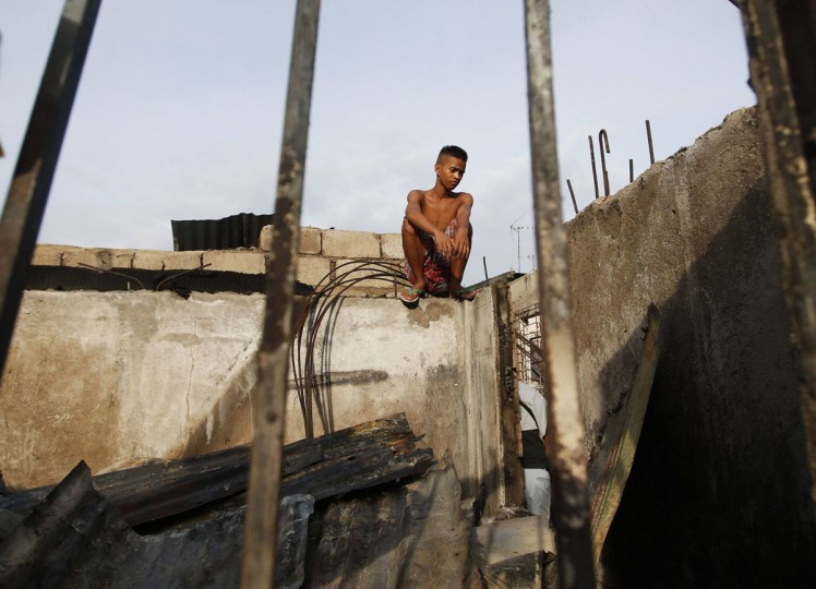 A fire victim looks at the ruins of his house razed by a fire in Paranaque, Metro Manila September 16, 2014. Some 100 families were left homeless after 60 houses in the neighbourhood of Paranaque were destroyed by a fire caused by faulty electrical wiring on Monday evening, local media said. (REUTERS/Erik De Castro)