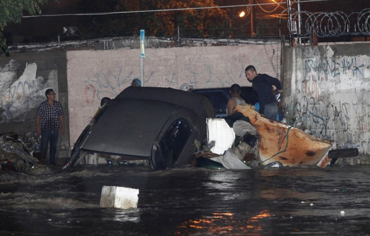People try to salvage a car that was swept away in a flooded street after tropical storm Odile hit the area with heavy rains, in Ciudad Juarez late September 17, 2014. About 25,000 tourists were also still trapped on the Baja California peninsula after tropical storm Odile on Monday felled trees, buffeted homes and business and smashed shops open to looters as tropical storm Polo became a hurricane off Mexico's Pacific coast on Wednesday night, the U.S. National Hurricane Centre said. Picture taken September 17, 2014. (Jose Luis Gonzalez/Reuters)