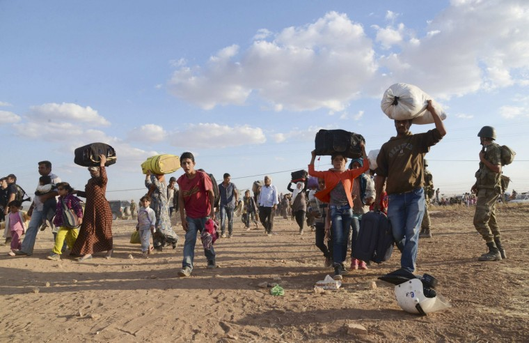 Syrian Kurds walk with their belongings after crossing into Turkey at the Turkish-Syrian border, near the southeastern town of Suruc in Sanliurfa province. About 60,000 Syrian Kurds fled into Turkey in the space of 24 hours, a deputy prime minister said on Saturday, as Islamic State militants seized dozens of villages close to the border. Turkey opened a stretch of the frontier on Friday after Kurdish civilians fled their homes, fearing an imminent attack on the border town of Ayn al-Arab, also known as Kobani. A Kurdish commander on the ground said Islamic State had advanced to within 15 km (9 miles) of the town.(Reuters)