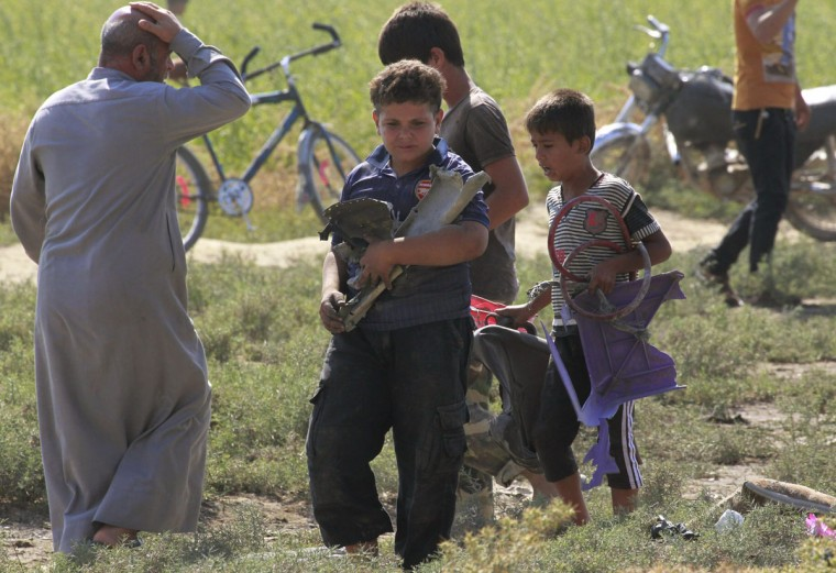 Children carry pieces of the wreckage of a war plane that crashed on the outskirts of Raqqa in northeast Syria September 16, 2014. Islamic State fighters shot down the Syrian war plane using anti-aircraft guns on Tuesday, the first time the group has downed a military jet since declaring its cross-border caliphate in June, the Syrian Observatory for Human Rights, which has been monitoring the civil war, said. (REUTERS/Stringer)