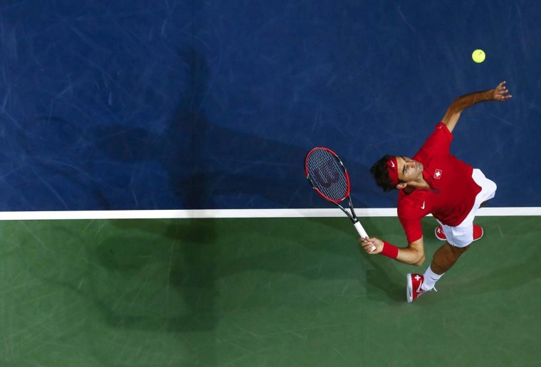 Switzerland's Roger Federer serves a ball during his Davis Cup semi-final tennis match against Italy's Simone Bolelli at the Palexpo in Geneva September 12. || PHOTO CREDIT: REUTERS - DENIS  BALIBOUSE