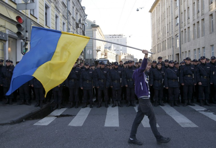 A man with a Ukrainian flag walks past riot police standing guard during an anti-war rally in Moscow. (Maxim Zmeyev/Reuters)