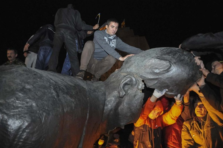 People react after a statue of Soviet state founder Vladimir Lenin was toppled by protesters during a rally organized by pro-Ukraine supporters in the centre of the eastern Ukrainian town of Kharkiv September 28, 2014. Picture taken September 28, 2014. (Reuters)