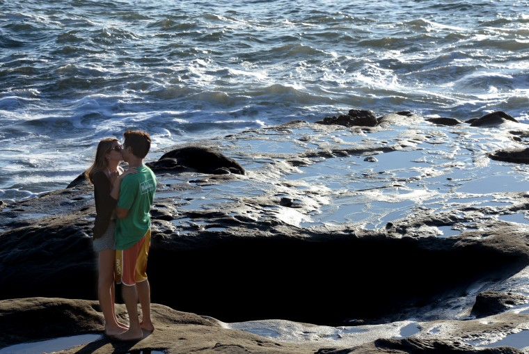 A young couple kisses on the rocks by the water of the Pacific Ocean at Sunset Cliffs in San Diego, Saturday, Aug. 23.