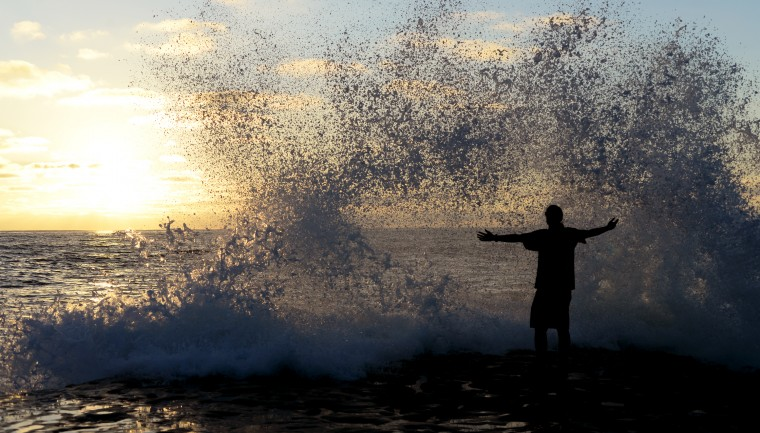 A man stands on the edge, enjoying a wave crashing over him as the sun sets.