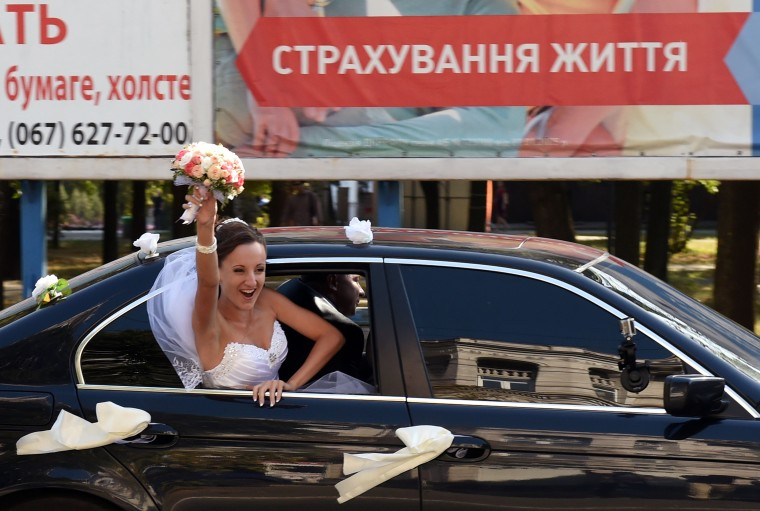 A Ukrainian bride celebrates her wedding while in her car in a street of the key southeastern port city of Mariupol after a ceasefire was signed the day before between Ukraine and pro-Kremlin insurgents. The guns remained silent over eastern Ukraine as a truce between Ukraine and pro-Kremlin insurgents appeared to be holding despite concerns it will fail to halt the separatist drive in the east. (Philippe Desmazes/AFP-Getty Images)