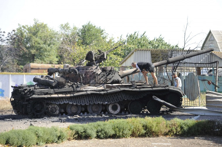 Villagers check a destroyed tank in the yard of a kindergarten in the village of Talakovka, some 22 kms northeast of Mariupol, a day after the signing of a 12-point pact backed by both Kiev and Moscow to end a conflict, which triggered the most serious crisis between Russia and the West since the Cold War. Ukraine said on September 6 that a truce was largely holding in the war-battered east, despite fears it may ultimately fail to halt a pro-Russian insurgency still threatening to tear the country apart. (Alexander Khudoteply/AFP-Getty Images)