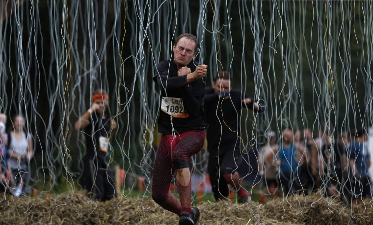 "A participant runs through the ""Electroshock Therapy"" obstacle, made of hanging electrical wire holding some 10,000 Volts, at the finish of the ""Tough Mudder"" endurance event series in Arnsberg. Competitors who took part in the endurance event saw themselves having to overcome various military style obstacles. (Ina Fassbender/Reuters)"