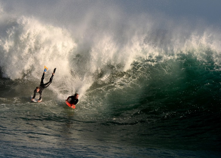 """Bodyboarders ride storm generated waves at """"The Wedge' break in Newport Beach, California. The southern Californian coast is being hit by its second set of large swells in 10 days, this time being generated by Cyclone Norbert. (Mark Ralston/AFP-Getty Images)"""