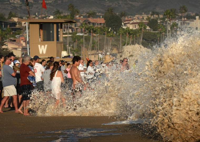 """A crowd is swamped by whitewash as they watch surfers ride storm generated waves at """"The Wedge"""" break in Newport Beach. The southern Californian coast is being hit by its second set of large swells in 10 days, this time being generated by Cyclone Norbert. (Mark Ralston/AFP-Getty Images)"""