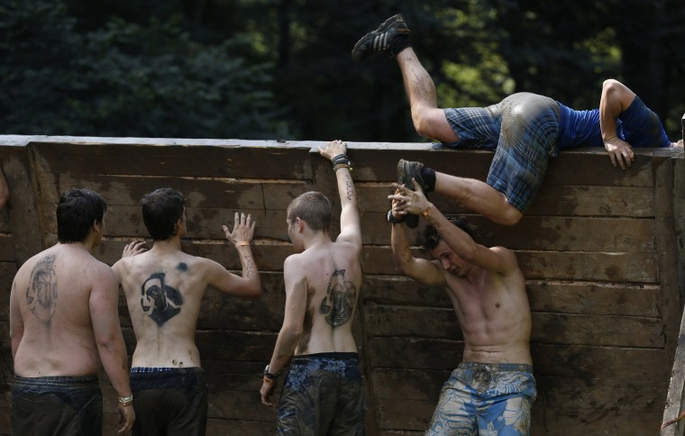 """Participants climb over a wall at the """"Tough Mudder"""" endurance event series in Arnsberg. Competitors who took part in the endurance event saw themselves having to overcome various military style obstacles. (Ina Fassbender/Reuters)"""