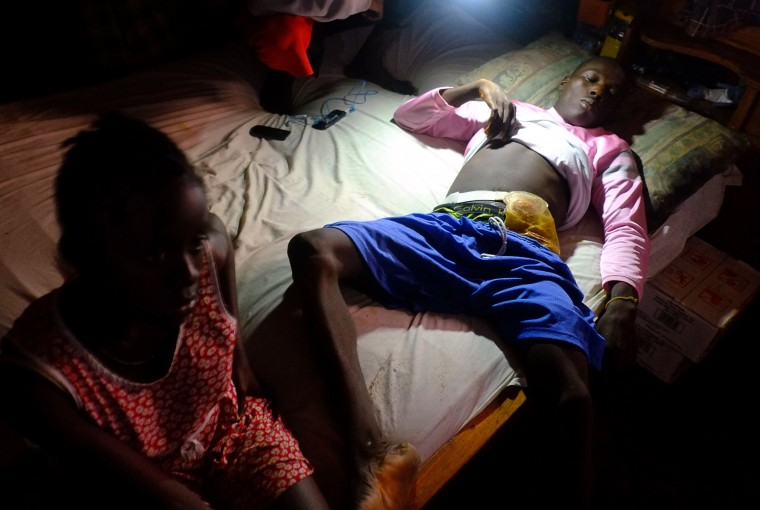 Titus Nauaha, wounded by soldiers during curfew on August 20, 2014, lies on a bed in his house in Monrovia's West Point slum. The death toll from the Ebola epidemic has climbed above 2,000, the World Health Organisztion (WHO) said on September 5, as it voiced hopes a vaccine could be available in November. The deadly virus has claimed 2,097 lives out of 3,944 people infected in Liberia, Guinea and Sierra Leone, since emerging in December 2013, the UN's health organ said after a two-day crisis meeting in Geneva. (Dominique FagetAFP-Getty Images)