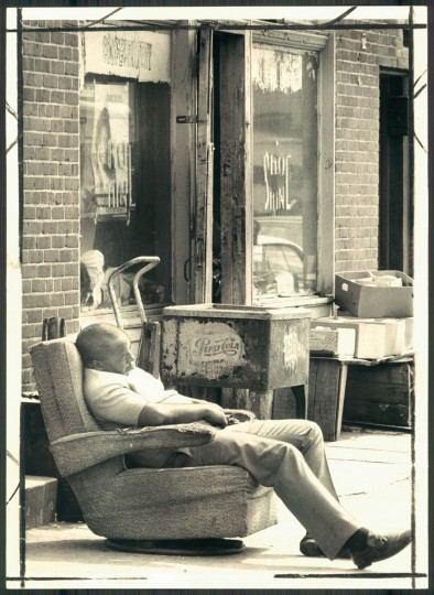 A man sleeps in front of a shoeshine parlor, resting up for Labor Day Weekend on Sept. 4, 1971. (William Laforce Jr./Baltimore Sun)