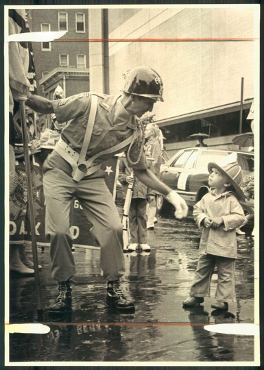 Chester Tippers, left, stops to chat with Joshua Hershberg, 2, at Cathedral and Centre during the Labor Day Parade on Sept. 1, 1975. (Ralph L. Robinson/Baltimore Sun)