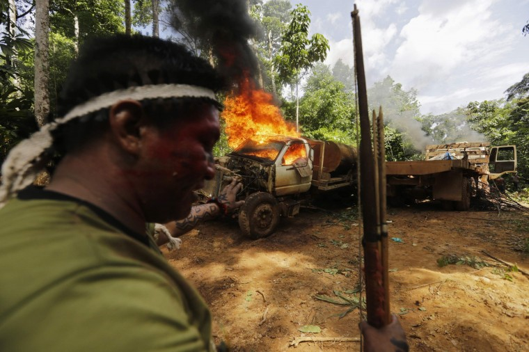 A Ka'apor Indian warrior stands near a burning logging truck during a jungle expedition to search for and expel loggers from the Alto Turiacu Indian territory, near the Centro do Guilherme municipality in the northeast of Maranhao state in the Amazon basin, August 7, 2014. Tired of what they say is a lack of sufficient government assistance in keeping loggers off their land, the Ka'apor Indians, who along with four other tribes are the legal inhabitants and caretakers of the territory, have sent their warriors out to expel all loggers they find and set up monitoring camps in the areas that are being illegally exploited. Picture taken August 7, 2014. (Lunae Parracho/Reuters)