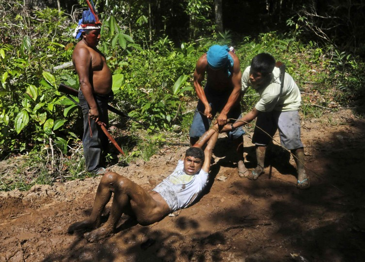 Ka'apor Indian warriors tie up and remove the pants of a logger during a jungle expedition to search for and expel loggers from the Alto Turiacu Indian territory, near the Centro do Guilherme municipality in the northeast of Maranhao state in the Amazon basin, August 7, 2014. Tired of what they say is a lack of sufficient government assistance in keeping loggers off their land, the Ka'apor Indians, who along with four other tribes are the legal inhabitants and caretakers of the territory, have sent their warriors out to expel all loggers they find and set up monitoring camps in the areas that are being illegally exploited. Picture taken August 7, 2014. (Lunae Parracho/Reuters)