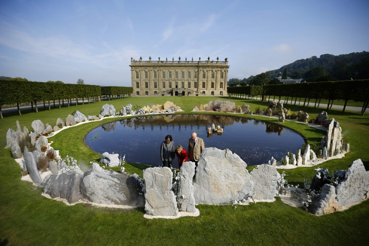 """The Duke and Duchess of Devonshire look at a piece by Chinese artist Xu Bing (L) entitled """"Tao Hua Yuan: A Lost Village Utopia"""" during the Beyond Limits selling exhibition at Chatsworth House in central England September 4, 2014. (Darren Staples/Reuters)"""